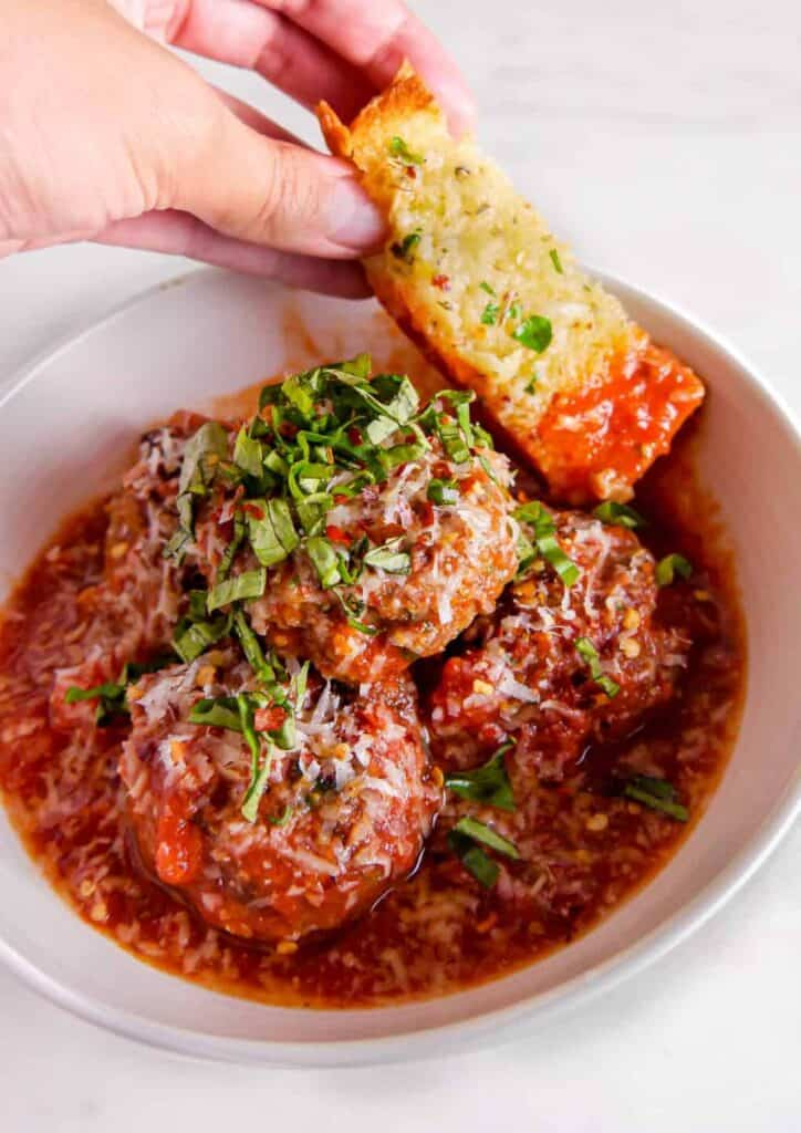 white bowl with meatballs stacked with fresh basil and garlic bread scooping up sauce