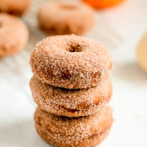 three pumpkin donuts stacked on each other