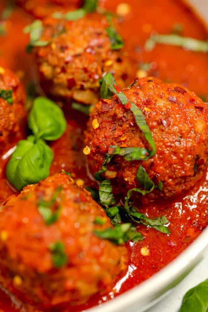 close up of meatball in red sauce with fresh basil chopped on top