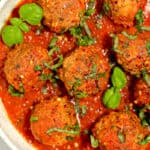 meatballs in a bowl of red sauce with fresh herbs on top and red pepper flakes