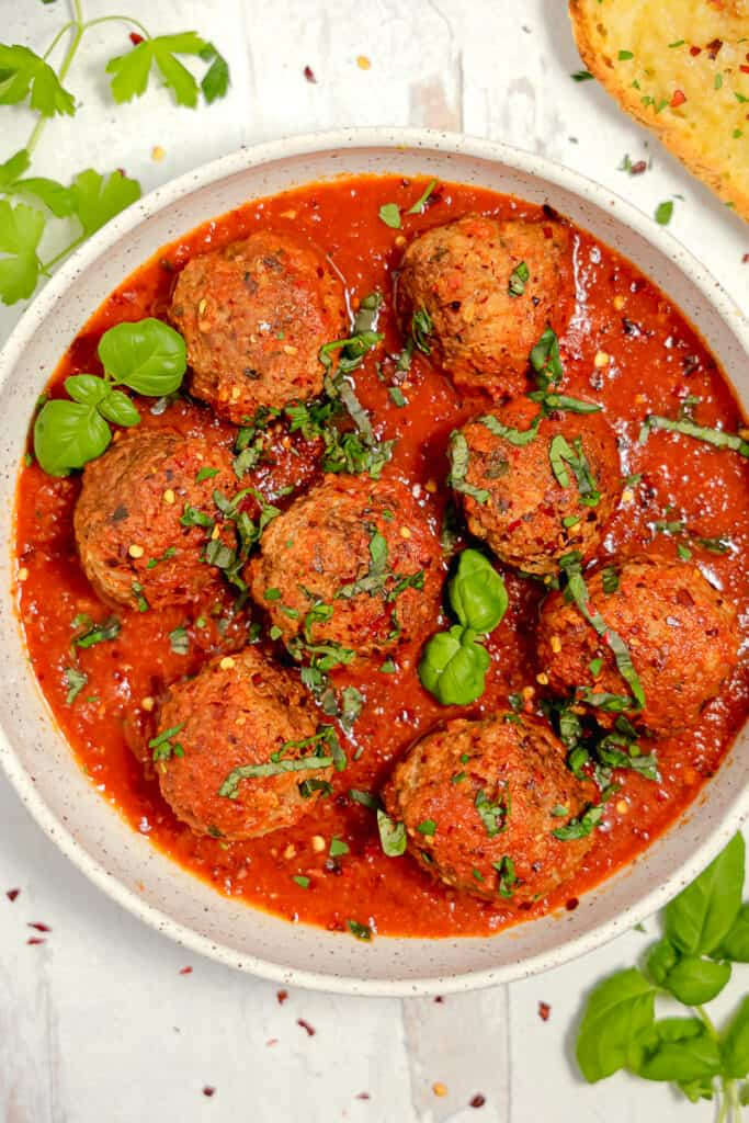 meatballs in a bowl of red sauce and fresh herbs over the top
