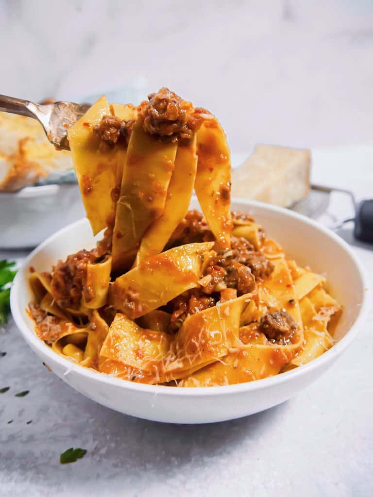 bowl of pappardelle bolognese being lifted out of the bowl with a fork