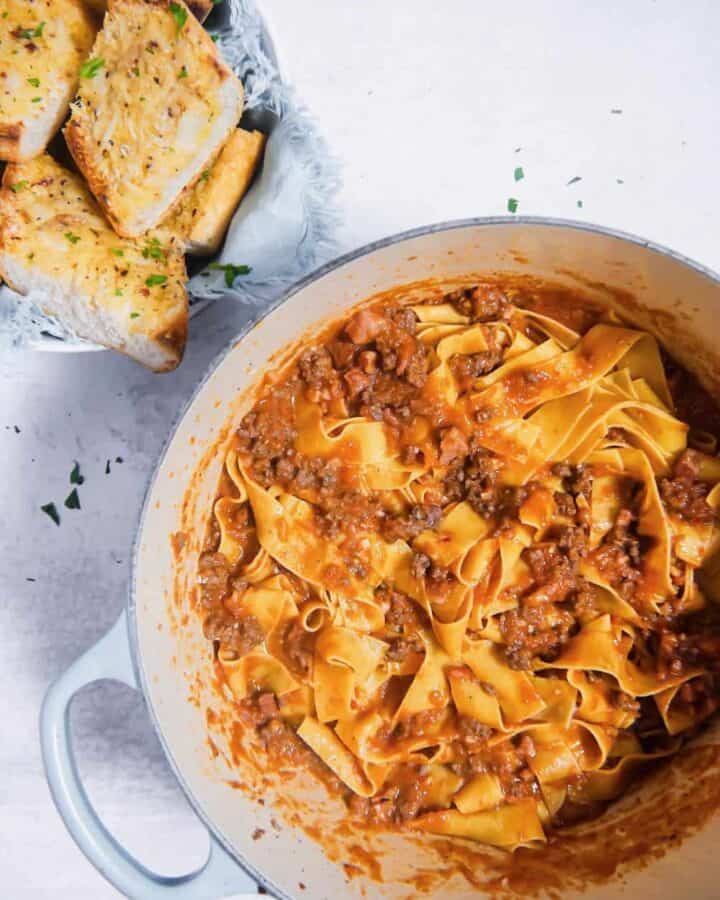 an overhead shot of bolognese sauce mixed with pappardelle pasta and garlic bread in a bowl to the side