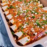 close up of chicken enchiladas in a baking dish topped with cilantro and cheese