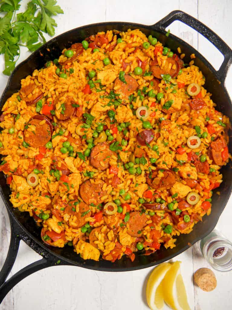 overhead photo of a cast iron skillet with paella inside and lemon wedges surrounding