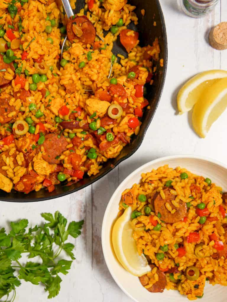 overhead photo of cast iron skillet with paella and a small bowl with chicken chorizo paella surrounded by herbs