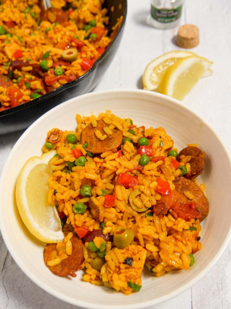 close up of bowl of paella with a lemon wedge