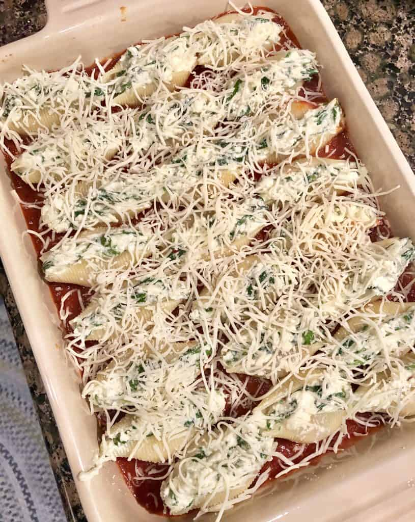 baking dish with spicy red sauce on the bottom, filled with stuffed shells and cheese on top pre oven