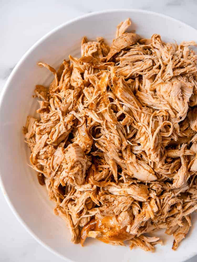 overhead photo of shredded chicken in a white bowl