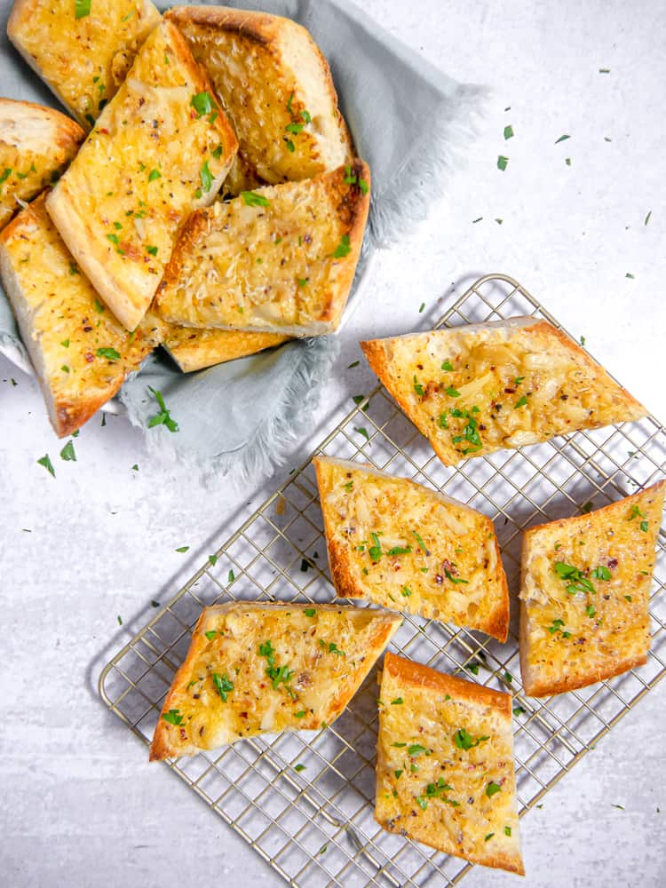garlic bread on a wire rack next to basket of garlic bread