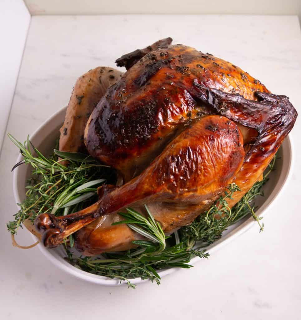 side shot of brined turkey with crispy skin in a white bowl with fresh herbs between turkey legs