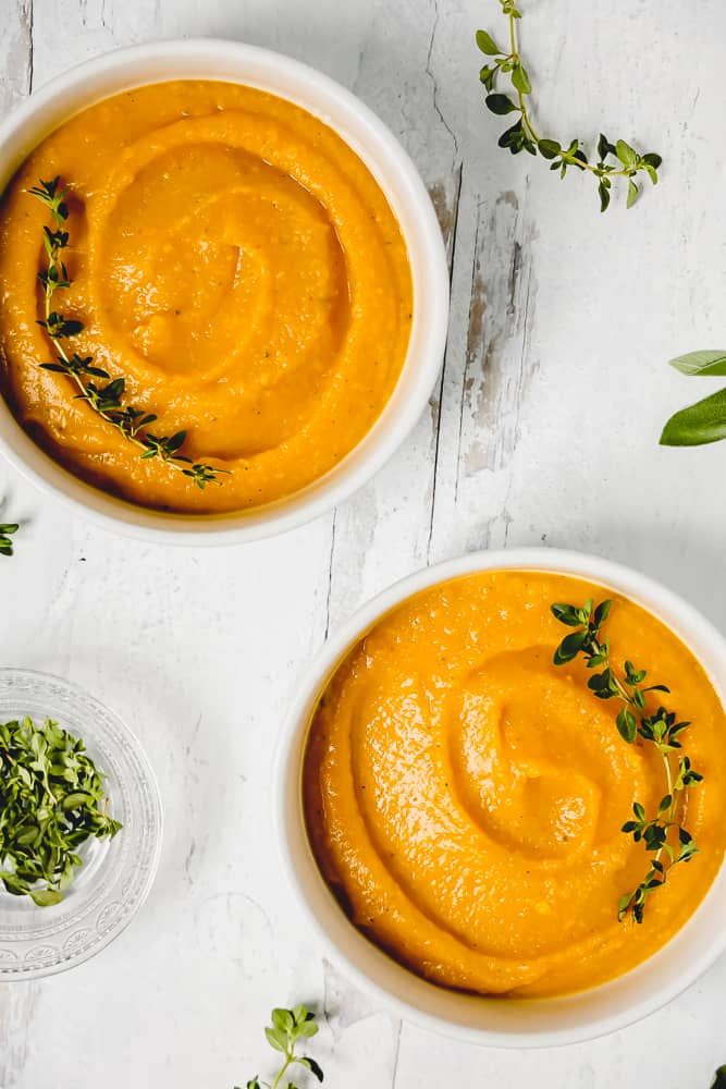 two white bowls with butternut squash soup surrounded by fresh thyme and sage