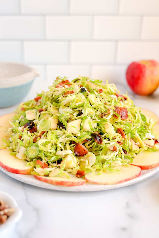 shaved brussels sprout salad surrounded by sliced apples with bacon, goat cheese and pecans