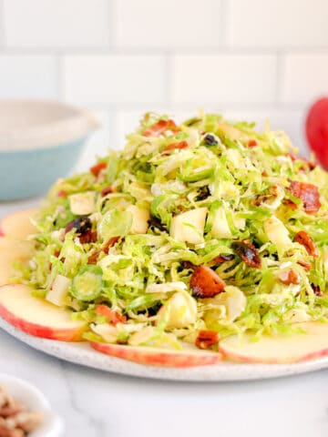 close up of shaved brussels sprouts surrounded by apples