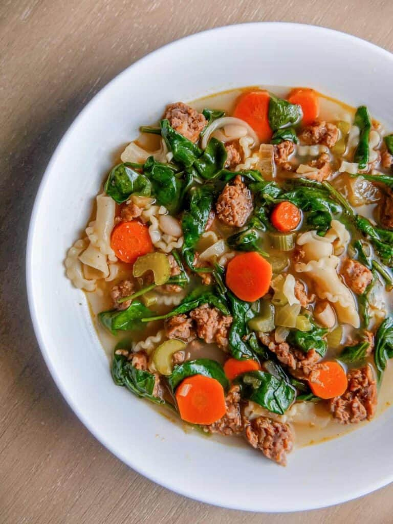 overhead shot of italian sausage white bean soup with carrots, spinach, and pasta in a white bowl