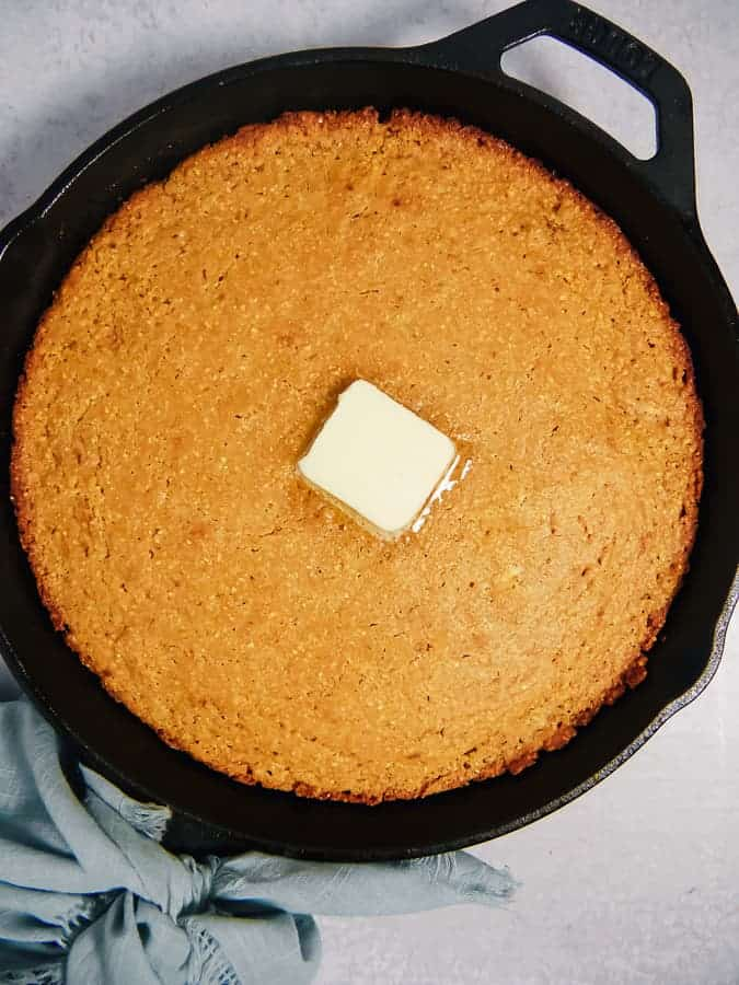 cast iron with corn bread inside and melting butter in the middle