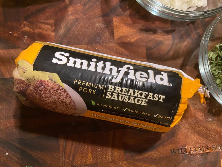 breakfast sausage in its casing on a cutting board