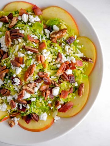 overhead shot of bowl with sliced apples surrounding, ahaved brussels sprouts, pecans, and goat cheese piled high as a salad
