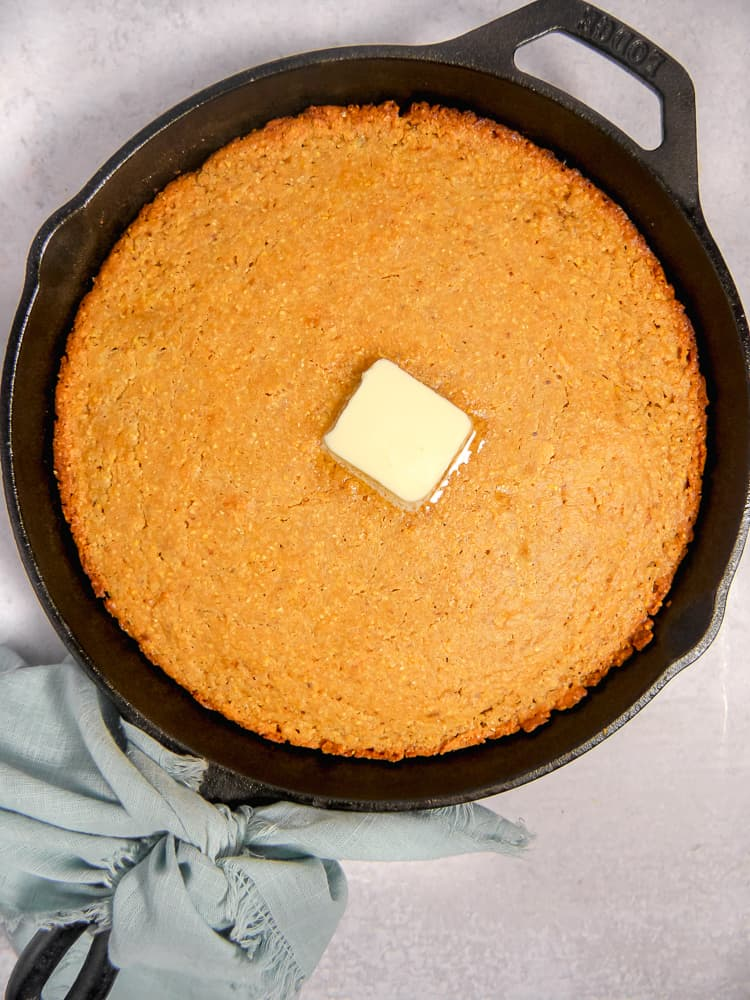 cast iron skillet with cornbread and melted butter in the center