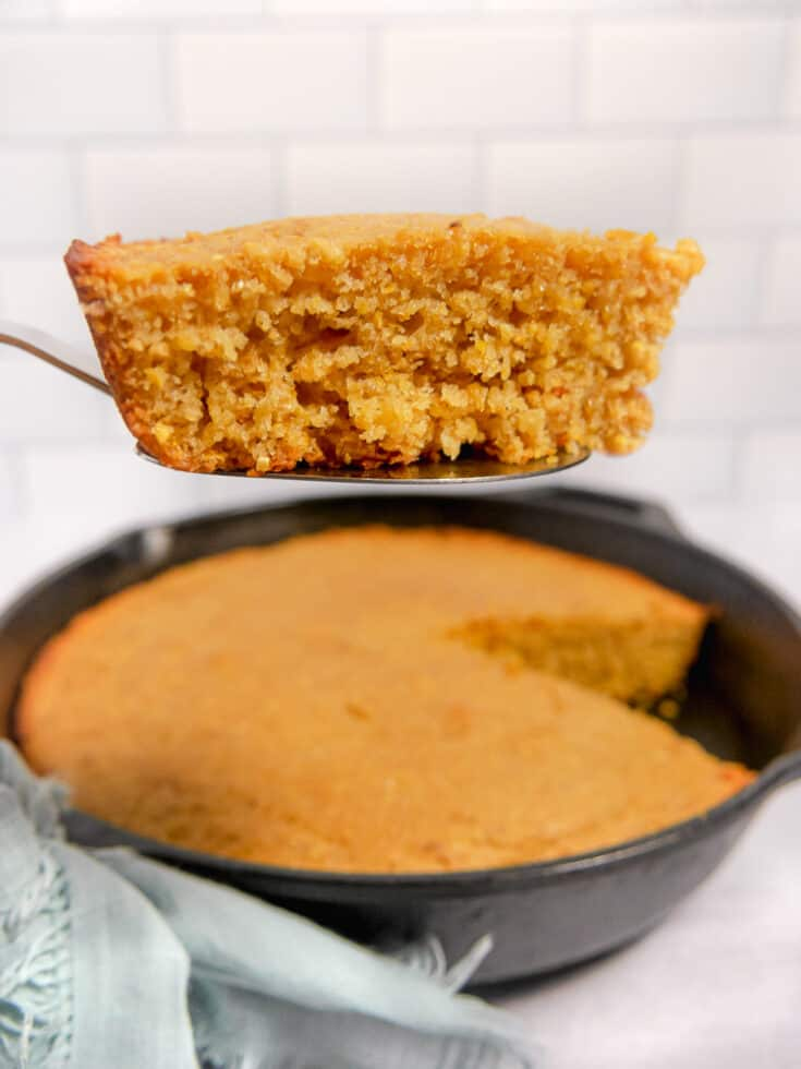 slice of cornbread on a serving spoon with cast iron in background