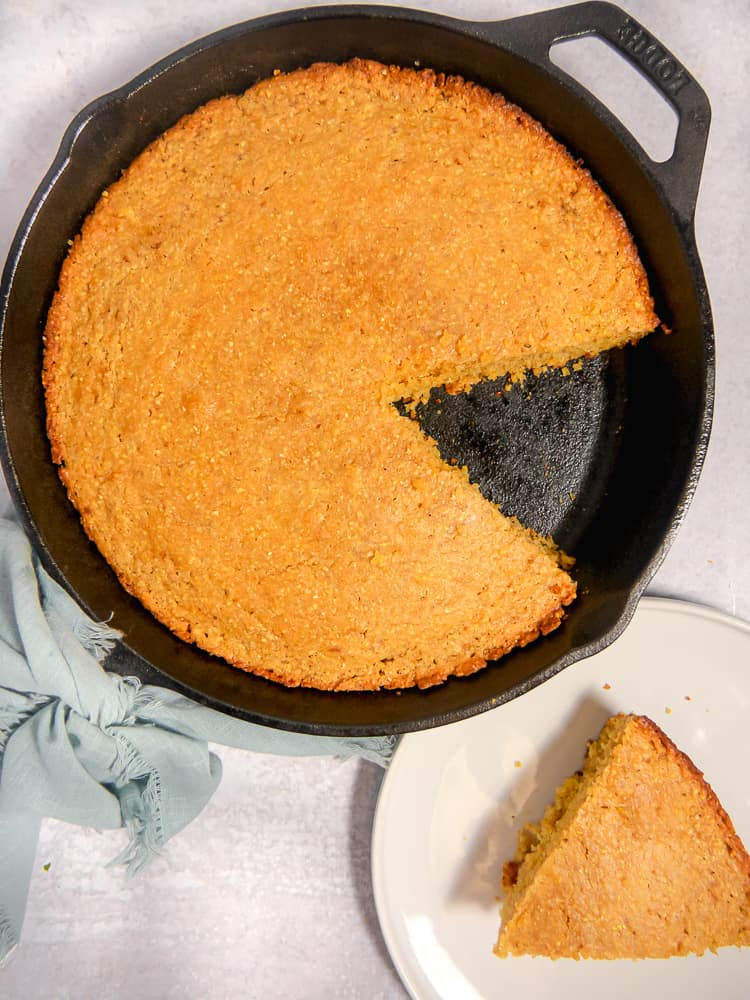 cornbread in a cast iron skillet with a piece cut out on a plate