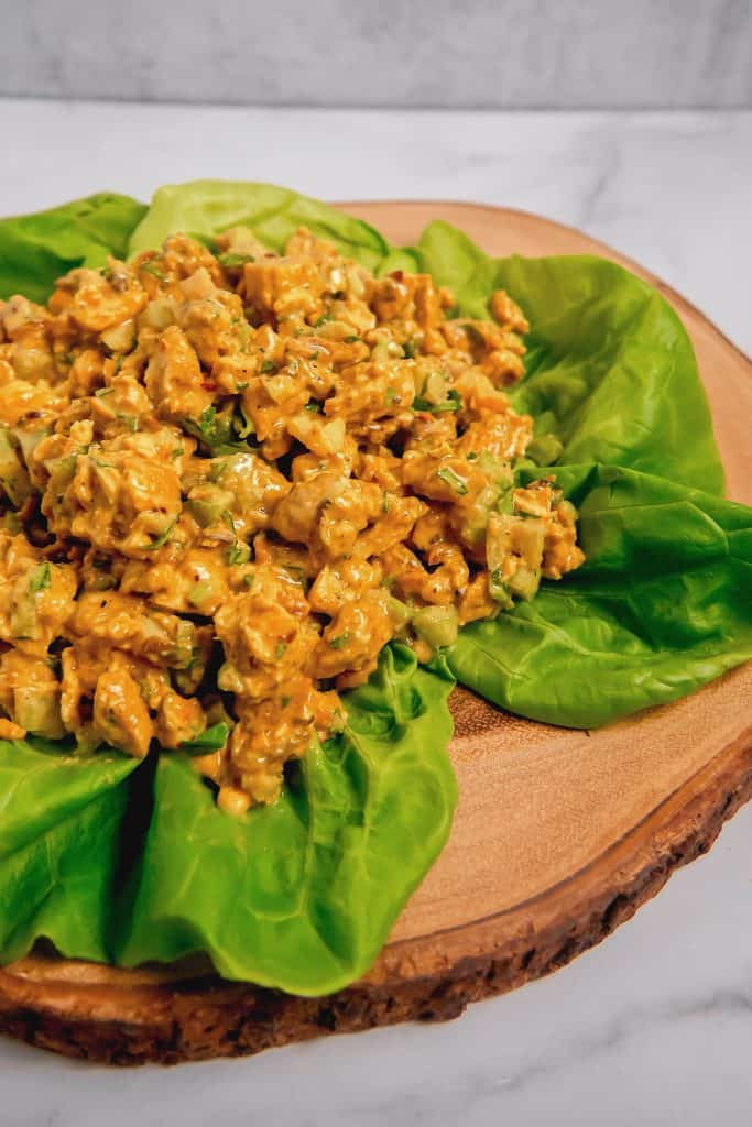 curry chicken salad on a bed of lettuce on a wooden plate