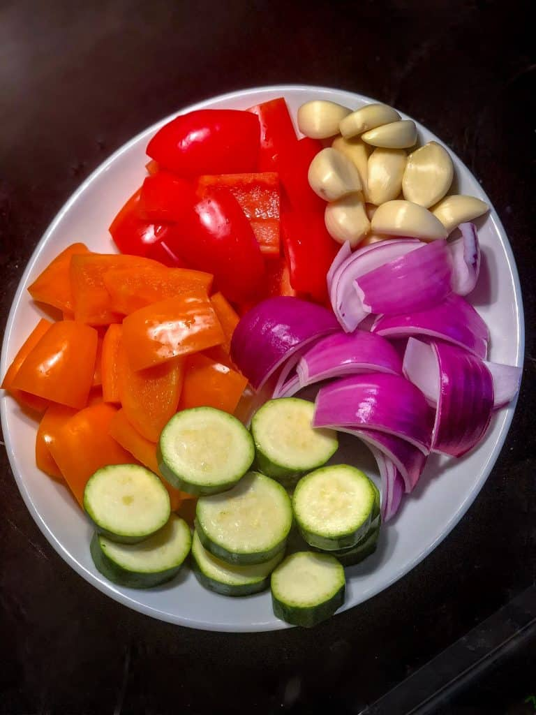 plate filled with chopped vegetables for skewers