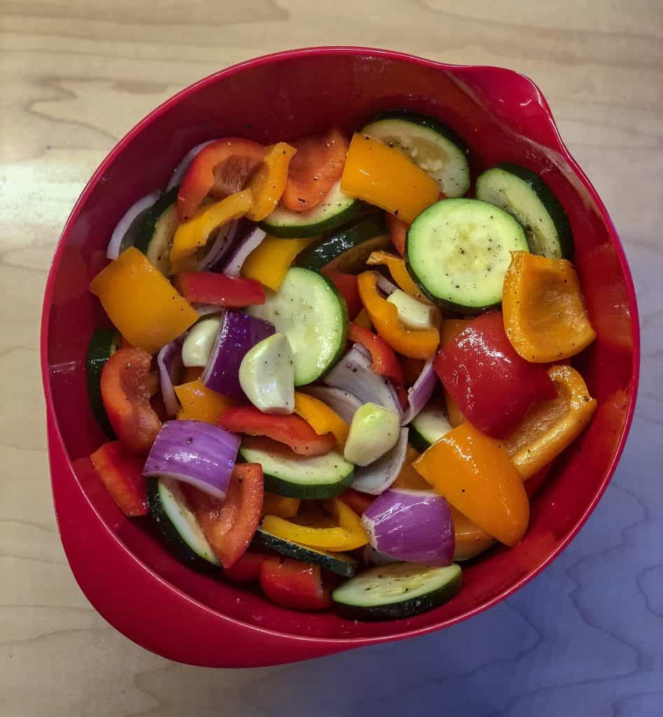 chopped vegetables in a red bowl tossed in olive oil