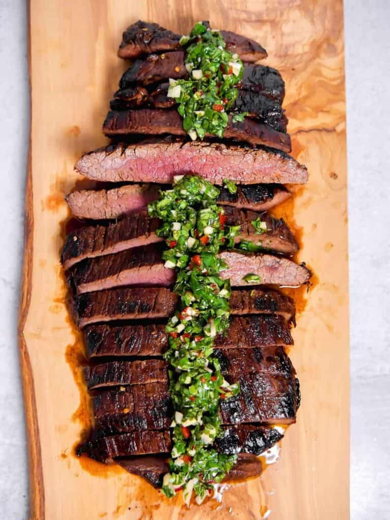 sliced flank steak on a cutting board with chimichurri on top