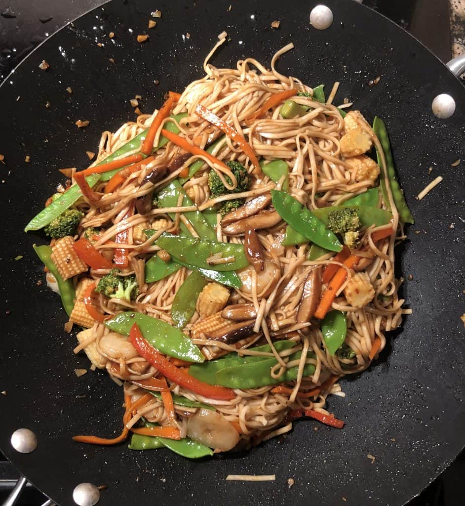 picture of vegetable lo mein in a wok being cooked together