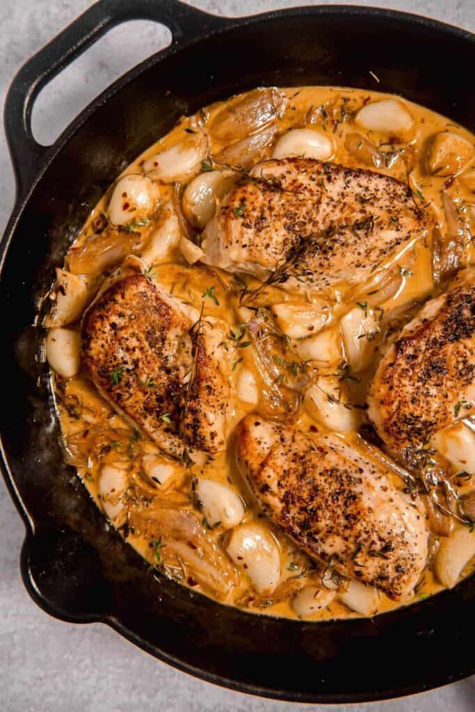 overhead picture of a cast iron skillet with chicken surrounded by garlic and a white wine sauce
