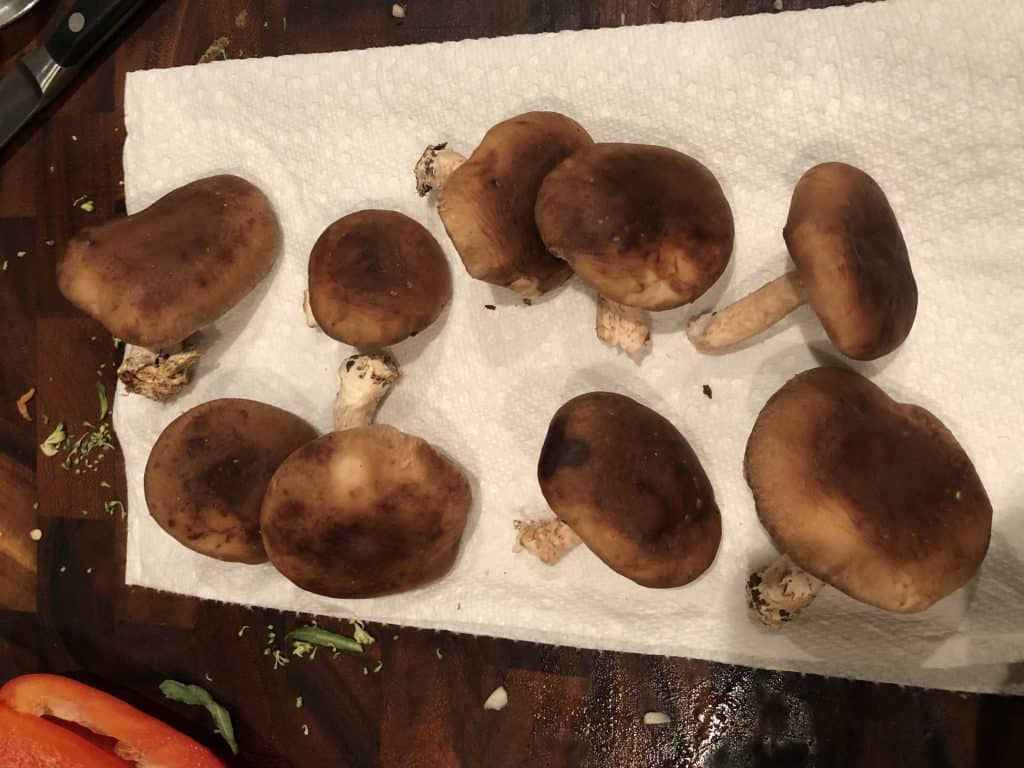 whole mushrooms on a cutting board post cleaning