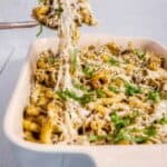 Pesto chicken pasta bake pulling out of baking dish