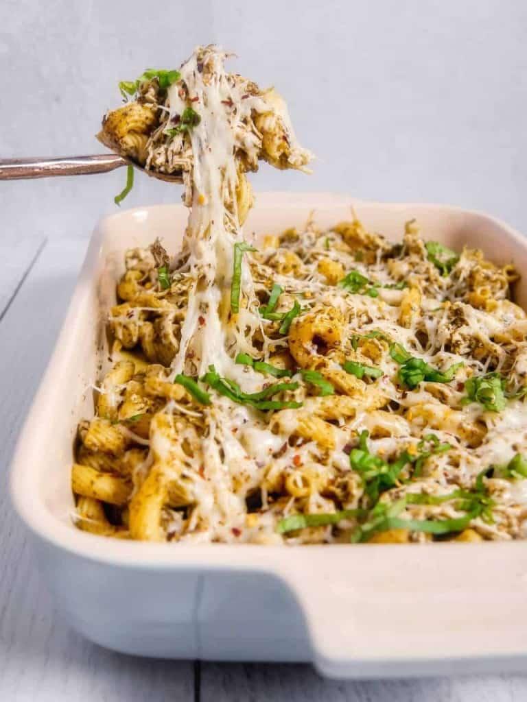 Pesto chicken pasta bake pulling out of baking dish
