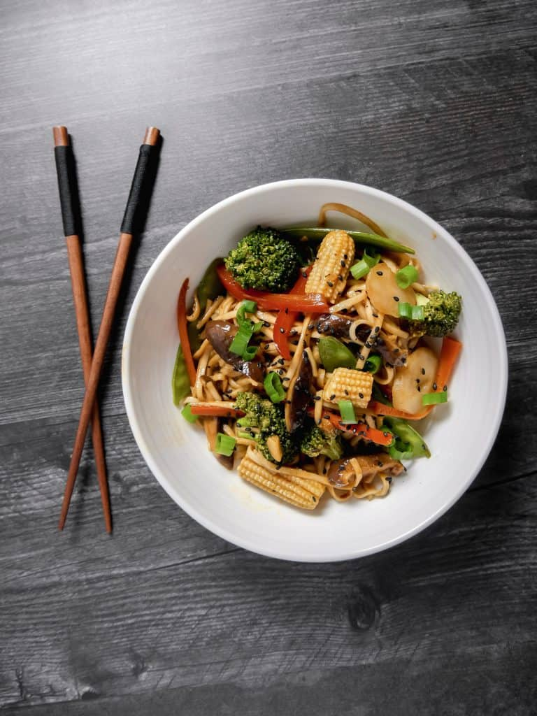 overhead shot of vegetable lo-mein in a bowl with chopsticks on the side