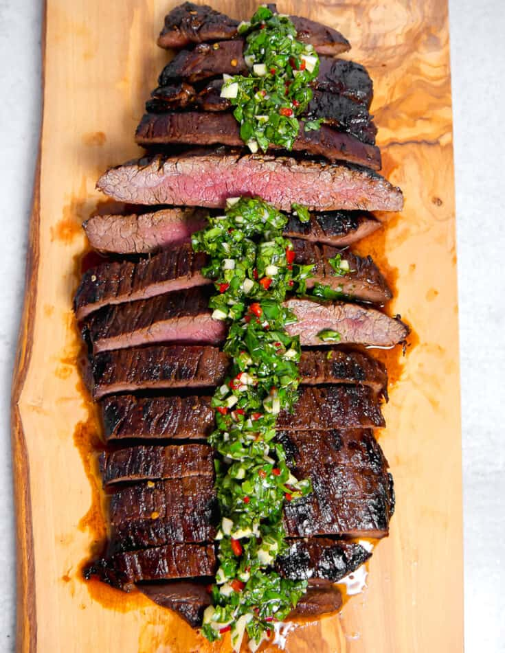 overhead photo of sliced flank steak on a wooden cutting board topped with chimichurri sauce