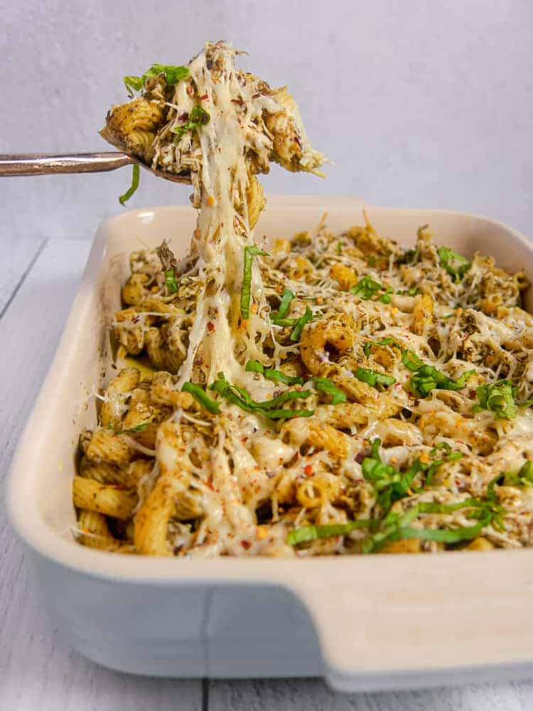 rectangular baking dish with pesto pasta and melty cheese being lifted out of the dish with a spoon