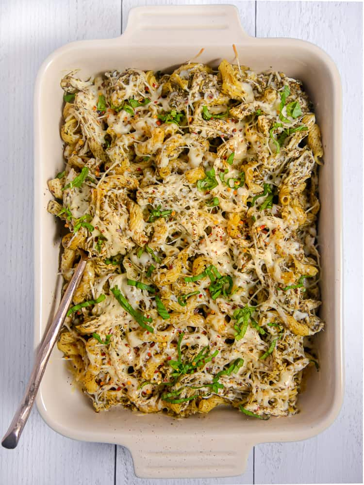 rectangular baking dish with pesto pasta, chicken, and melty cheese over the top with fresh basil