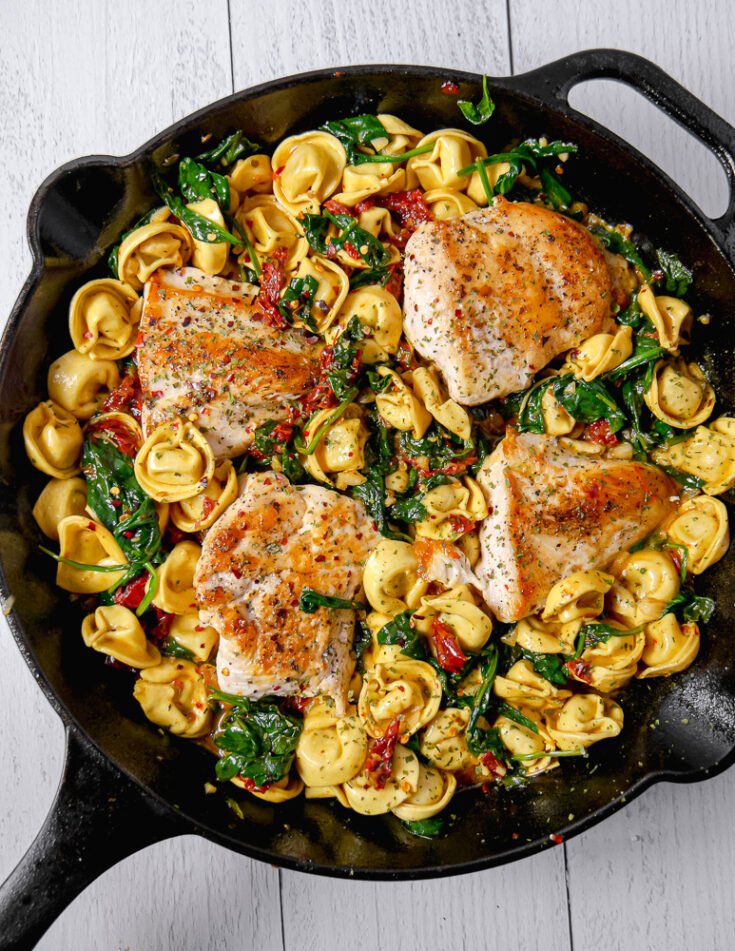 cast iron skillet with cheese tortellini, spinach, tomatoes, and seared chicken breast