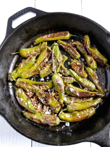 cast iron pan with blistered shishito peppers