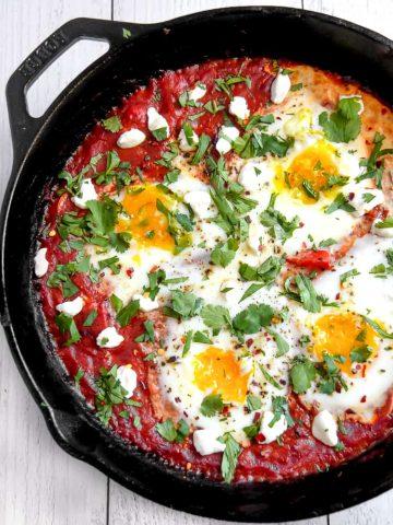 cast iron pan with shakshuka eggs inside