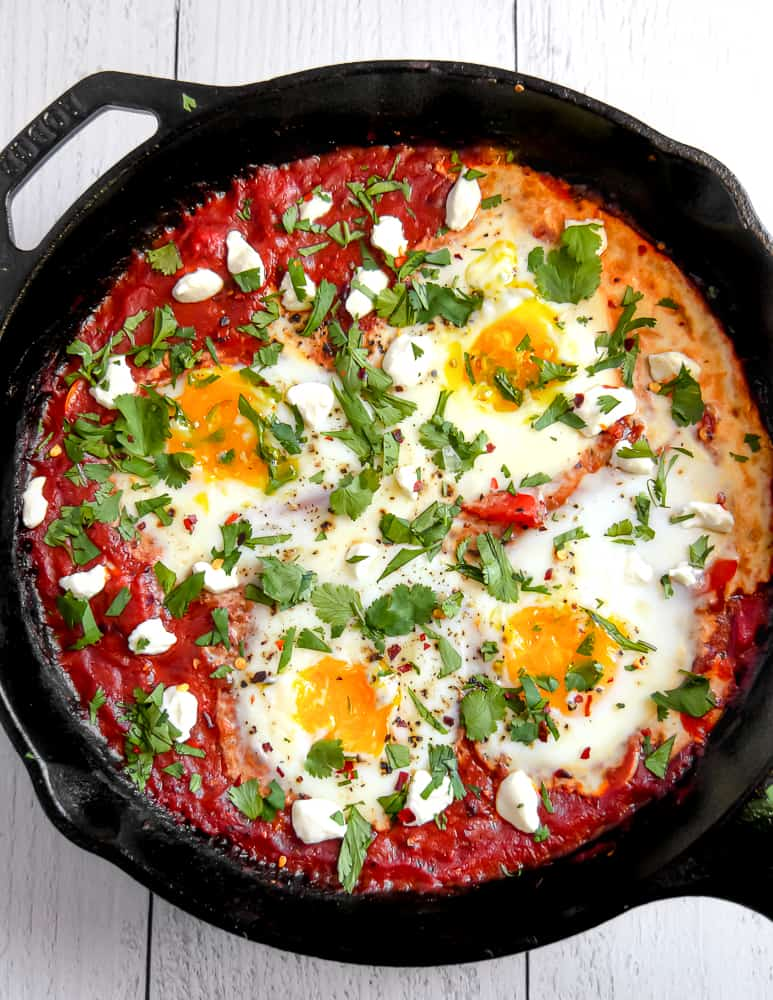 overhead photo of tomato sauce and baked eggs topped with cheese and herbs in a cast iron skillet
