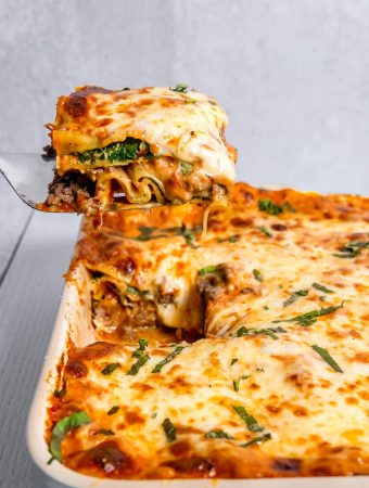 spinach and cheese lasagna being lifted out of rectangular baking dish