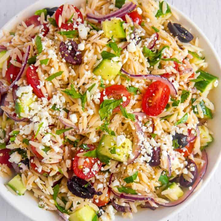 overhead photo of white bowl filled with orzo and greek ingredients