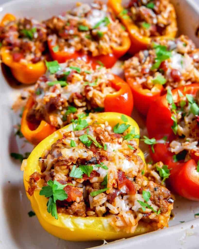 several hot italian sausage stuffed peppers in a baking dish with rice, melted cheese, and cilantro on top