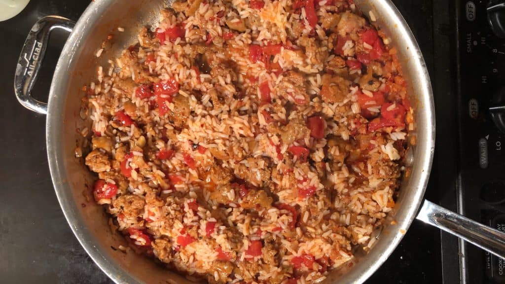 large skillet on the stove top with rice, hot italian sausage, and tomatoes inside