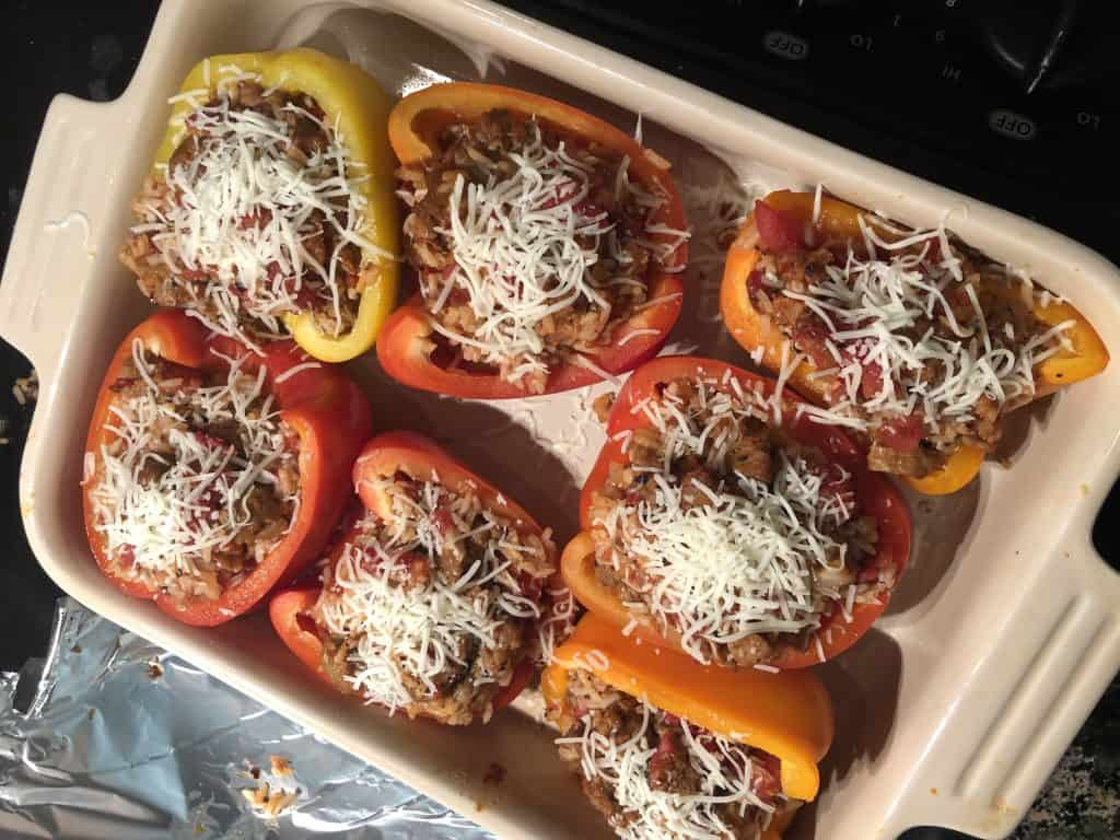 7 bell peppers in a baking dish with stuffing inside and unmelted cheese sprinkled on top
