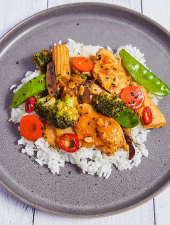 Chicken stir fry with vegetables on a grey plate