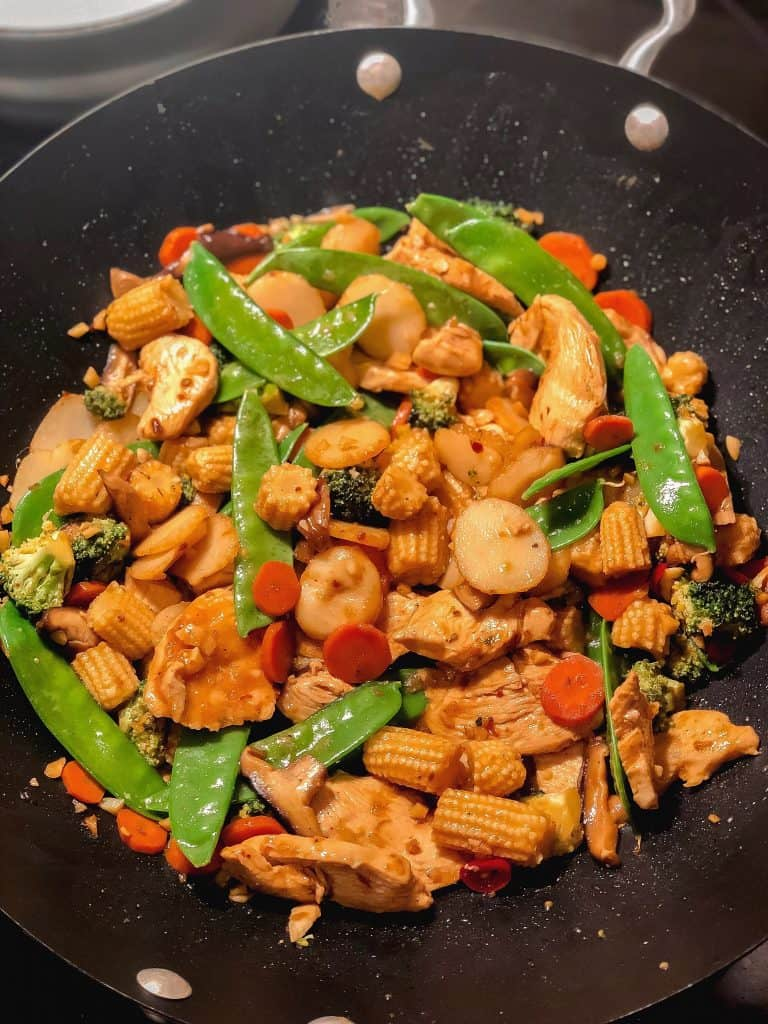Spicy chicken stir fry with vegetables in a wok