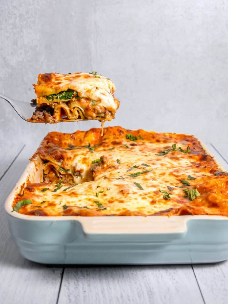spinach and beef lasagna being lifted out of baking dish with brown bubbly cheese